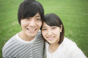 草原で微笑むカップルの写真素材 [FYI04557233]