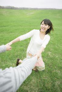 草原で手をつなぐカップルの写真素材 [FYI04557239]