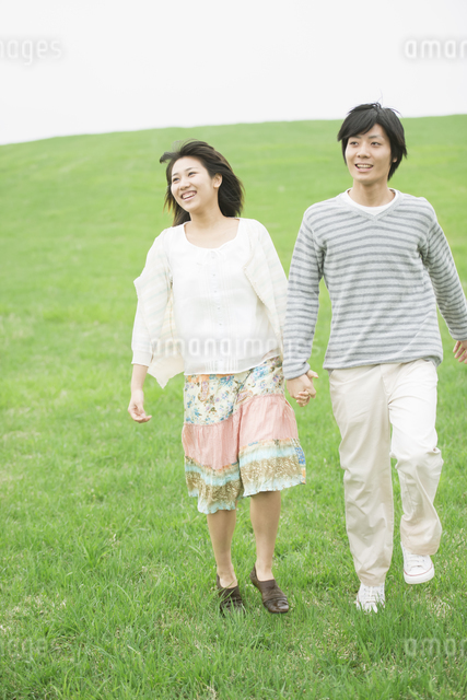 草原で手をつなぐカップルの写真素材 [FYI04557241]