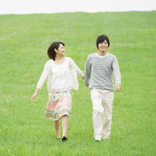 草原で手をつなぐカップルの写真素材 [FYI04557242]
