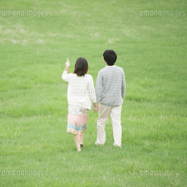 草原で手をつなぐカップルの後姿の写真素材 [FYI04557246]