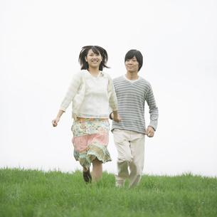 草原を走るカップルの写真素材 [FYI04557252]