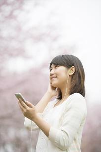 桜の前で音楽を聴く女性の写真素材 [FYI04557277]