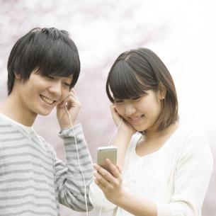 桜の前で音楽を聴くカップルの写真素材 [FYI04557281]
