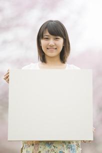 桜の前でメッセージボードを持つ女性の写真素材 [FYI04557308]