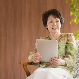 タブレットPCを持ち微笑むシニア女性の写真素材 [FYI04557372]