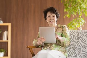 タブレットPCを持ち微笑むシニア女性の写真素材 [FYI04557373]