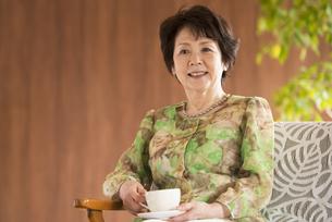 コーヒーカップを持ち微笑むシニア女性の写真素材 [FYI04557384]