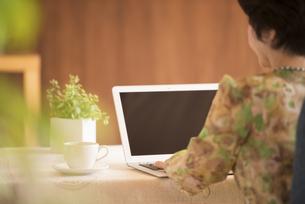 ノートパソコンを操作するシニア女性の後姿の写真素材 [FYI04557398]