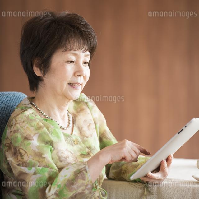 タブレットPCを操作するシニア女性の写真素材 [FYI04557407]