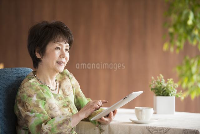 タブレットPCを操作するシニア女性の写真素材 [FYI04557411]