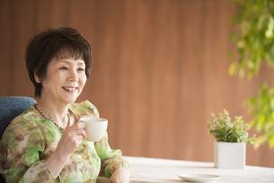 コーヒーカップを持ち微笑むシニア女性の写真素材 [FYI04557416]