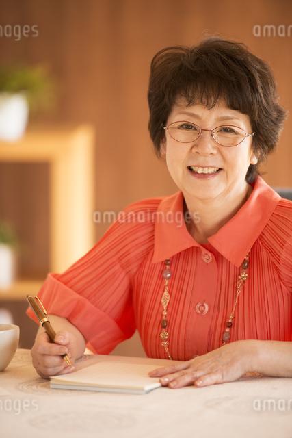 手紙を書くシニア女性の写真素材 [FYI04557428]