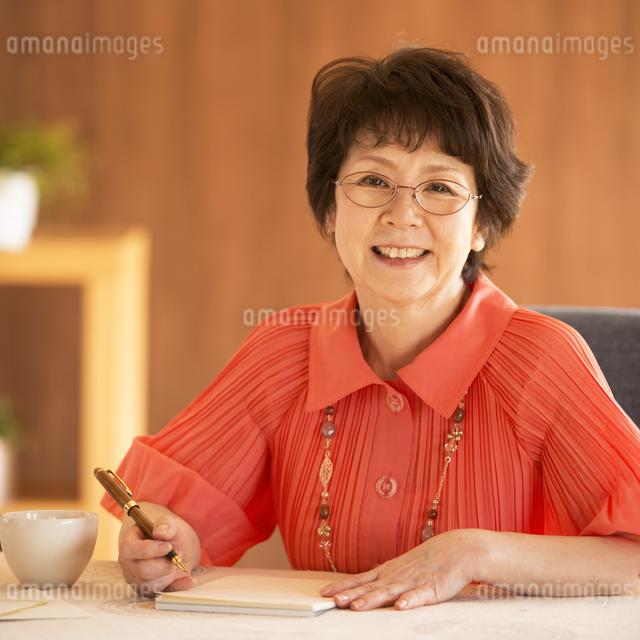 手紙を書くシニア女性の写真素材 [FYI04557430]