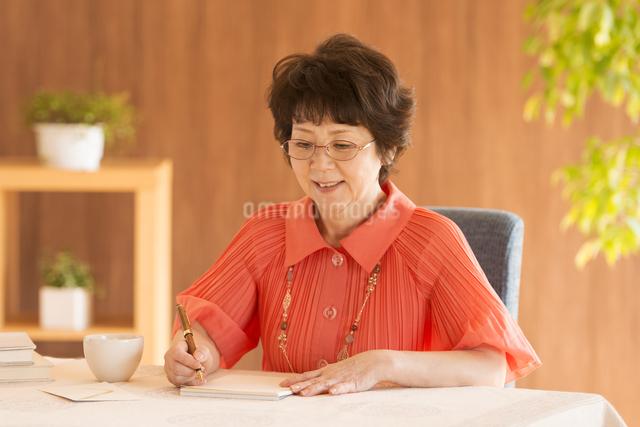 手紙を書くシニア女性の写真素材 [FYI04557438]