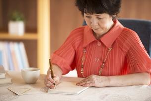 手紙を書くシニア女性の写真素材 [FYI04557442]