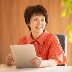 タブレットPCを持ち微笑むシニア女性の写真素材 [FYI04557464]