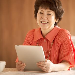 タブレットPCを持ち微笑むシニア女性の写真素材 [FYI04557471]