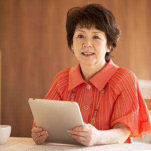タブレットPCを持ち微笑むシニア女性の写真素材 [FYI04557472]