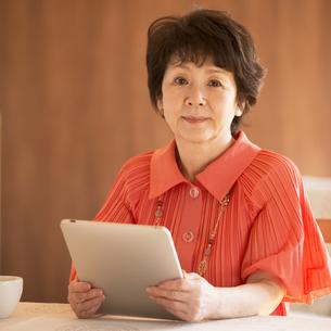 タブレットPCを持ち微笑むシニア女性の写真素材 [FYI04557474]