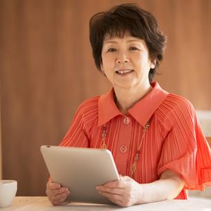 タブレットPCを持ち微笑むシニア女性の写真素材 [FYI04557475]
