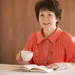 コーヒーカップを持ち微笑むシニア女性の写真素材 [FYI04557481]
