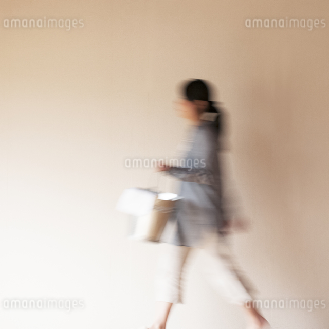 掃除用具を持ち部屋を歩く女性の写真素材 [FYI04557483]