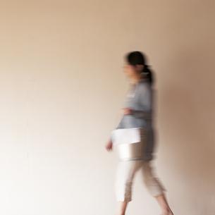 掃除用具を持ち部屋を歩く女性の写真素材 [FYI04557484]