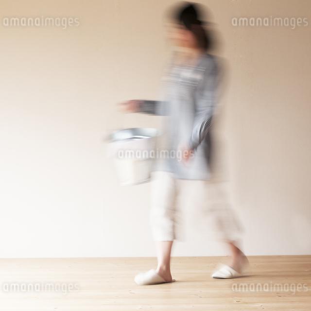掃除用具を持ち部屋を歩く女性の写真素材 [FYI04557485]