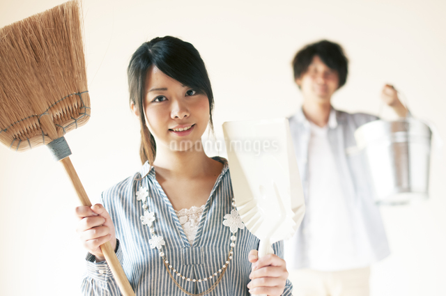 掃除用具を持ち微笑むカップルの写真素材 [FYI04557486]