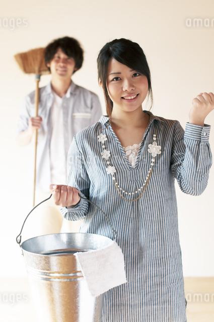 掃除用具を持ちガッツポーズをするカップルの写真素材 [FYI04557487]