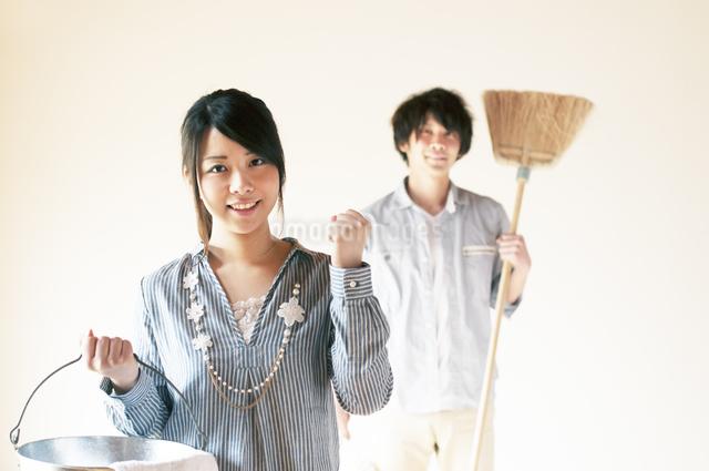 掃除用具を持ちガッツポーズをするカップルの写真素材 [FYI04557489]