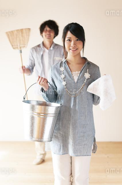 掃除用具を持ち微笑むカップルの写真素材 [FYI04557490]