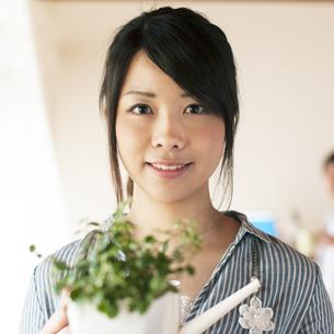 じょうろを持ち微笑む女性の写真素材 [FYI04557500]