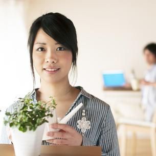 じょうろを持ち微笑む女性の写真素材 [FYI04557501]