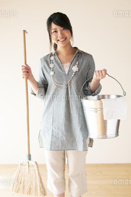 掃除用具を持ち微笑む女性の写真素材 [FYI04557517]