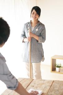 ほうきで掃除をする女性とテーブルを拭く男性の写真素材 [FYI04557518]