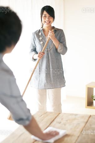 ほうきで掃除をする女性とテーブルを拭く男性の写真素材 [FYI04557520]