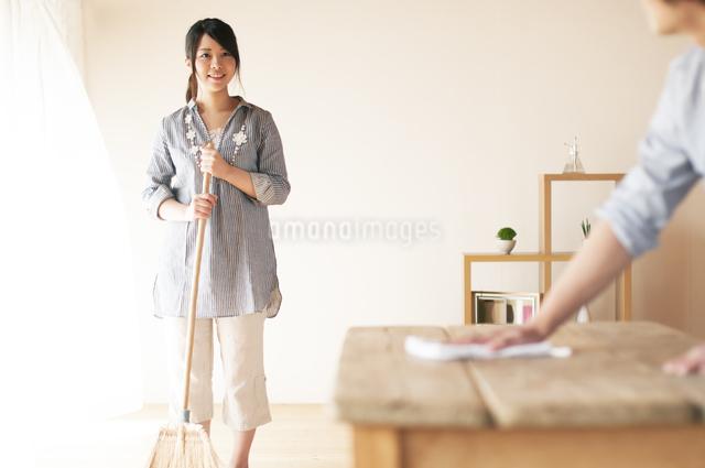 ほうきで掃除をする女性とテーブルを拭く男性の写真素材 [FYI04557521]