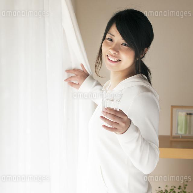 グラスを持ちカーテンを開ける女性の写真素材 [FYI04557526]