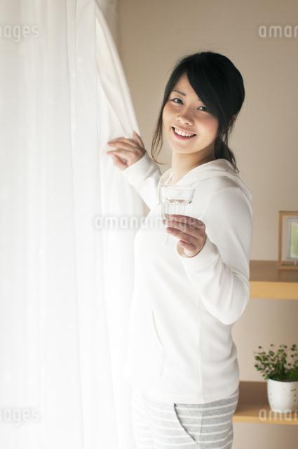 グラスを持ちカーテンを開ける女性の写真素材 [FYI04557527]