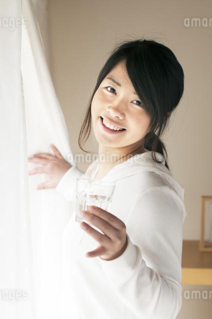 グラスを持ちカーテンを開ける女性の写真素材 [FYI04557528]