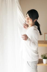 グラスを持ちカーテンを開ける女性の写真素材 [FYI04557530]