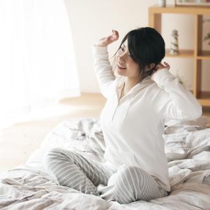 ベッドで伸びをする女性の写真素材 [FYI04557531]