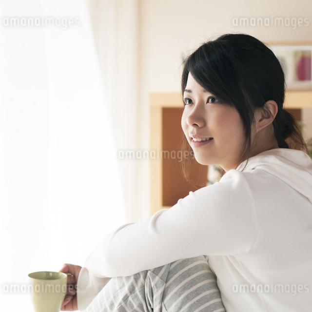 コーヒーカップを持ち微笑む女性の写真素材 [FYI04557533]