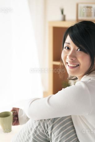 コーヒーカップを持ち微笑む女性の写真素材 [FYI04557535]