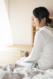 ベッドに座りコーヒーカップを持つ女性の写真素材 [FYI04557536]