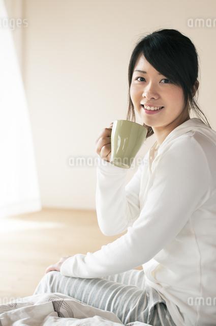 コーヒーカップを持ち微笑む女性の写真素材 [FYI04557537]