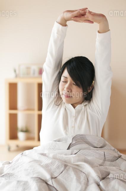 ベッドで伸びをする女性の写真素材 [FYI04557540]