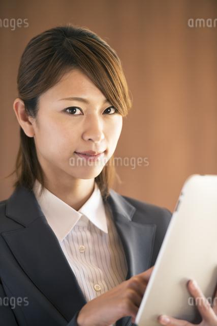 タブレットPCを操作するビジネスウーマンの写真素材 [FYI04557543]